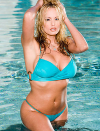 Stormy Daniels coming out of the pool with cool water running down her ample cleavage and dripping off her glistening butt.
